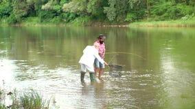 人渔夫抓一条鱼 鳟鱼的用假蝇钓鱼 用假蝇钓鱼是最显耀的作为捉住的鳟鱼一个方法 影视素材