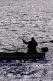 人渔的剪影从一条小船的 库存照片