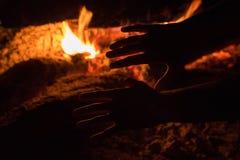 人温暖他的手在篝火的火焰在黑暗的夜 免版税库存照片