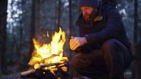 人温暖自己在阵营火在森林里 库存图片