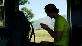 人游人在火车使用一个智能手机,当坐一个美好的山风景和小山的背景时 股票视频