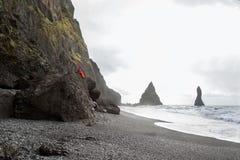 人游人坐在一座山在冰岛,概念顶部  免版税库存图片