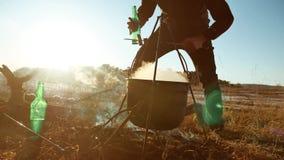 人游人是坐由篝火在自然野营的剪影阳光日落的止步不前党的远足者啤酒 供以人员 影视素材