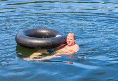 人游泳在与管的水中 库存图片