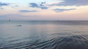 人游泳在日落期间的起波纹的海 股票视频