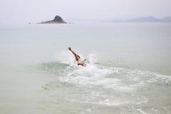 年轻人游泳在海洋 在海岛和银行半岛上的背景山 免版税图库摄影