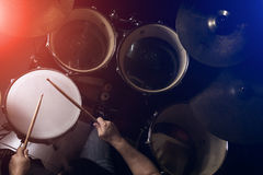 人演奏在低灯背景中设置的鼓 免版税库存图片