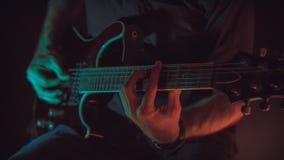 人演奏电吉他,深蓝和红色照明设备 免版税库存照片