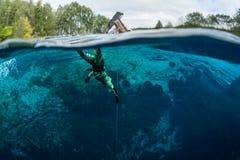 人潜水在一个蓝色透明的湖 免版税库存照片