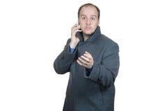 人灰色外套谈话在电话 免版税库存照片