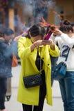 人灼烧的香火和祈祷在一个寺庙在中国 免版税库存照片