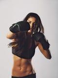 年轻人炫耀妇女训练拳击 免版税库存照片