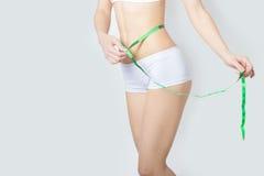 年轻人炫耀测量完善的形状好的臀部,一种健康生活方式的概念的一名美丽的亭亭玉立的妇女在白色背景的 库存图片