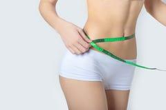 年轻人炫耀测量完善的形状好的臀部,一种健康生活方式的概念的一名美丽的亭亭玉立的妇女在白色背景的 免版税库存照片