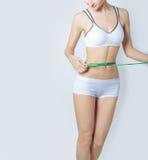 年轻人炫耀测量完善的形状好的臀部,一种健康生活方式的概念的一名美丽的亭亭玉立的妇女在白色背景的 免版税库存图片