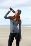 年轻人炫耀从瓶的妇女饮用水户外 免版税库存图片