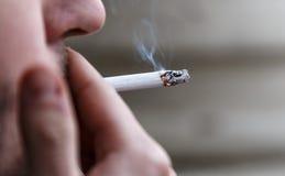 人点燃一根香烟并且抽烟 免版税库存照片