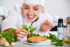 年轻人烹调与准备的三文鱼在专业厨房里 库存照片