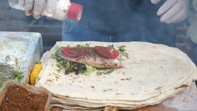 人烹调做与鱼在街市上,在手套特写镜头的手的ekmek 股票录像