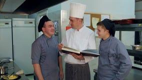 年轻人烹调有的实习生与拿着菜谱的厨师的正面讨论 股票录像
