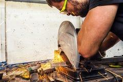 人焊工切开与一把圆锯的一种金属 免版税库存图片