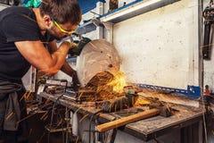 人焊工切开与一把圆锯的一种金属 免版税图库摄影
