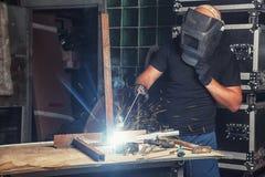 人焊接一个金属电弧焊接器 库存照片