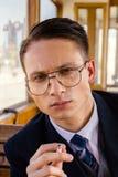 人照片戴眼镜的在坐在一老木wa的衣服 免版税图库摄影