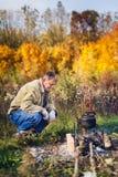 人煮沸在火的煤烟灰水壶 图库摄影