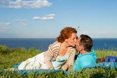 人爱恋的夫妇坐地面 日落的亲吻的人和女孩在云彩与天空 免版税图库摄影