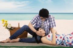年轻人爱抚他的海滩的女朋友 免版税库存图片