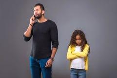 黑人父亲谈话在他的电话,当他女儿等待时 免版税库存照片