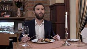 人特写镜头有坐在桌上的胡子的在餐馆 吃肉盘和享用伟大的食物 股票录像