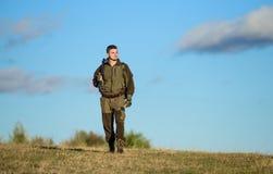 人狩猎自然环境 男性爱好活动 人猎人运载步枪天空蔚蓝背景 经验和 库存照片