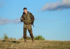 人狩猎自然环境 男性爱好活动 狩猎武器枪或步枪 人猎人运载步枪天空蔚蓝 库存照片