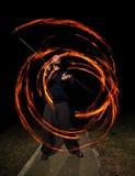年轻人玩杂耍的火poi 免版税库存照片