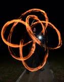 年轻人玩杂耍的火poi 库存照片
