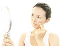 年轻人生气妇女有她的皮肤的问题 免版税库存照片