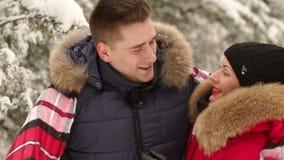 人用一条毯子盖他的女孩在一个多雪的公园 股票视频