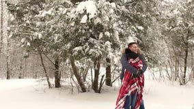 人用一条毯子盖他的女孩在冬天公园 股票视频