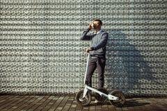 人用以现代大厦为背景的滑行车饮用的咖啡 库存照片