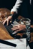 人用使用膝上型计算机的被绑住的手在木桌上 免版税库存图片