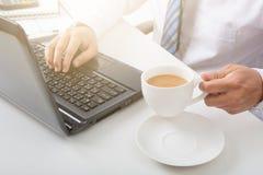 人用咖啡和研究的手膝上型计算机的膝上型计算机 图库摄影