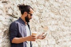 人用在城市街道上的智能手机饮用的咖啡 免版税库存照片