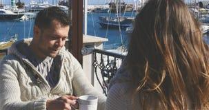 年轻人用在室外咖啡馆的热的咖啡 库存图片