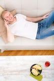 年轻人用在沙发的一个三明治 免版税库存图片