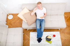 年轻人用在沙发的一个三明治 免版税库存照片