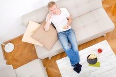 年轻人用在沙发的一个三明治 库存照片