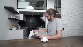 人用在现代厨房的报纸饮用的早晨咖啡 股票录像