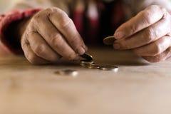 人用坐在他的书桌的肮脏的手计数硬币 库存照片